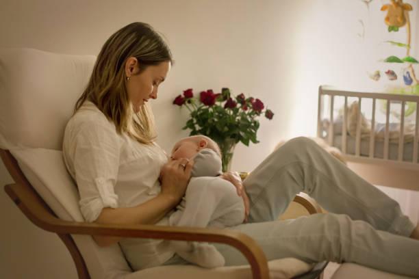 Joven hermosa madre, amamantando su bebé recién nacido en la noche, dim luz - foto de stock