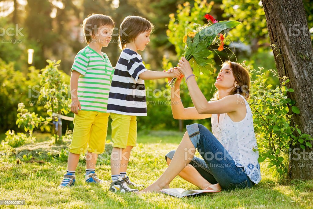Young beautiful mother, sitting in a garden, little boys, her sons, bringing gerbera flowers and present for her, mothers day surprise royalty-free stock photo