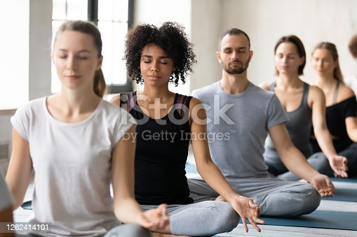 istock Young beautiful peaceful african american woman meditating with diverse people. 1262414101