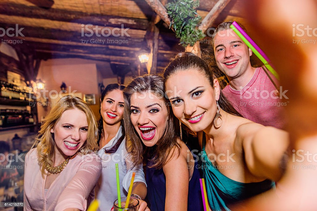 Young beautiful people with cocktails in bar taking selfie stock photo