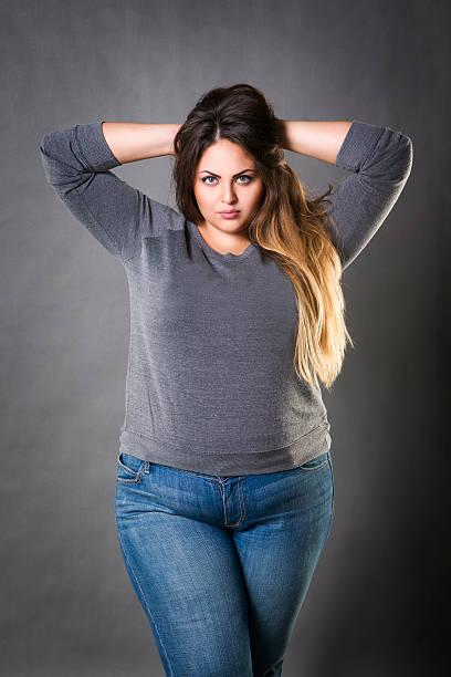 young beautiful plus size model in blue jeans, xxl woman - damen jeans übergrößen stock-fotos und bilder