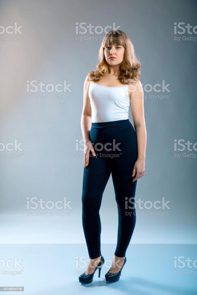 Young Beautiful Plus Size Model Wearing In Black Leggings And White ...