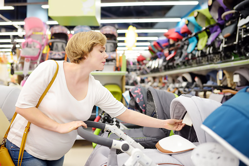 Young beautiful pregnant woman choosing baby stroller or pram buggy for newborn. Shopping for expectant mothers and baby.