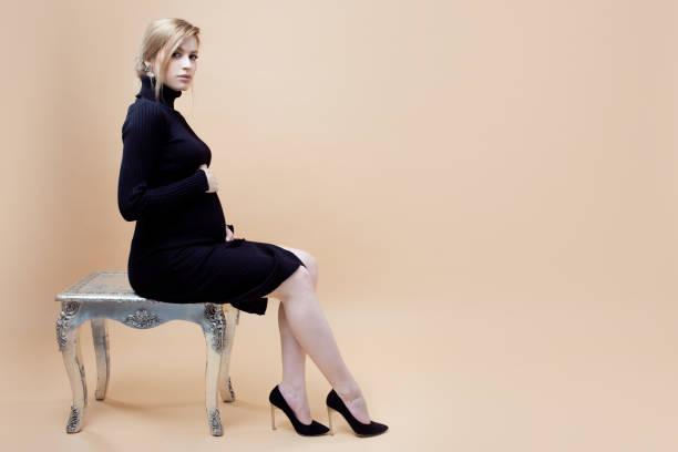 Una joven hermosa mujer embarazada con ropa negra y zapatos de tacón negro se sienta en un banco sobre fondo neutro. - foto de stock