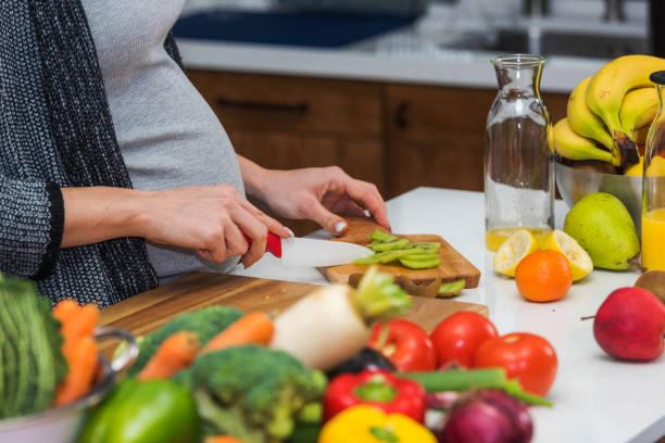 Junge, schöne schwangere Frau bereitet gesunde Mahlzeit mit Obst und Gemüse – Foto
