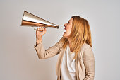 istock Young beautiful readhead businesswoman screaming using vintage megaphone 1205331429
