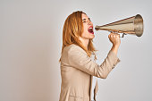 istock Young beautiful readhead businesswoman screaming using vintage megaphone 1205331443