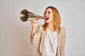 istock Young beautiful readhead businesswoman screaming using vintage megaphone 1205331444