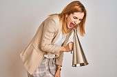 istock Young beautiful readhead businesswoman screaming using vintage megaphone 1205331446