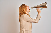 istock Young beautiful readhead businesswoman screaming using vintage megaphone 1205331454