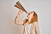 istock Young beautiful readhead businesswoman screaming using vintage megaphone 1205331455
