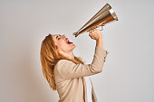 istock Young beautiful readhead businesswoman screaming using vintage megaphone 1205331473