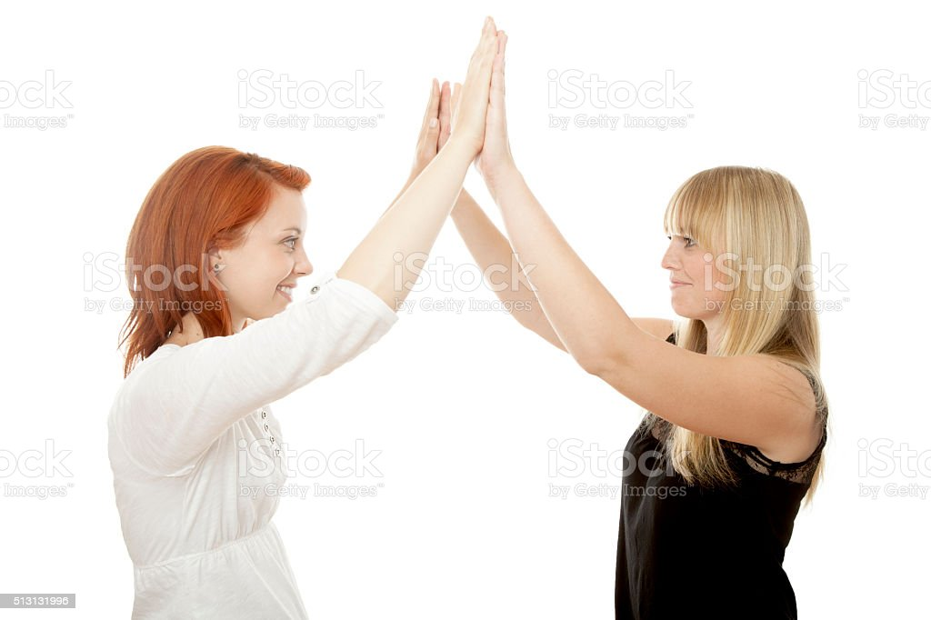 young beautiful red and blond haired girls high five stock photo