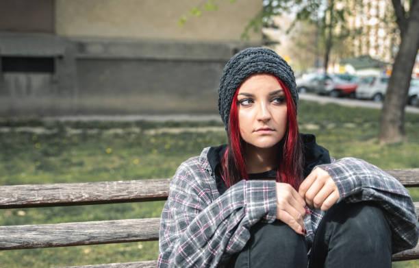 junge schöne rote haare mädchen sitzen allein im freien auf der holzbank mit hut und hemd gefühl ängstlich und deprimiert, nachdem sie eine obdachlose person aus nächster nähe porträt - rot bekümmerte möbel stock-fotos und bilder