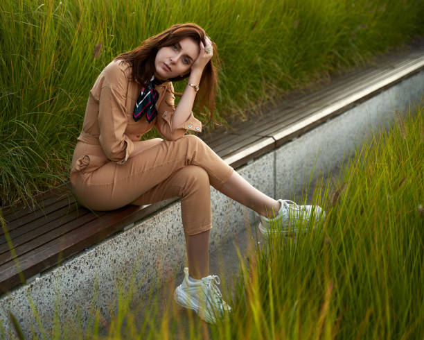 Young beautiful red haired gen z girl wearing slim fitted women beige khaki coverall overall denim jumpsuit or flight suit and white chunky platform sneakers sitting on a long park bench in high green grass. Thoughtful face expression. Young beautiful red haired gen z girl in slim fitted women beige khaki coverall overall denim jumpsuit or flight suit and flight suit stock pictures, royalty-free photos & images