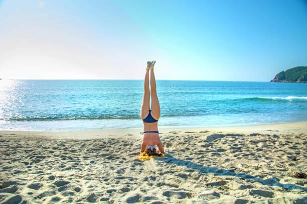 Junge, schöne, rothaarige Mädchen praktizieren Yoga am Strand. – Foto