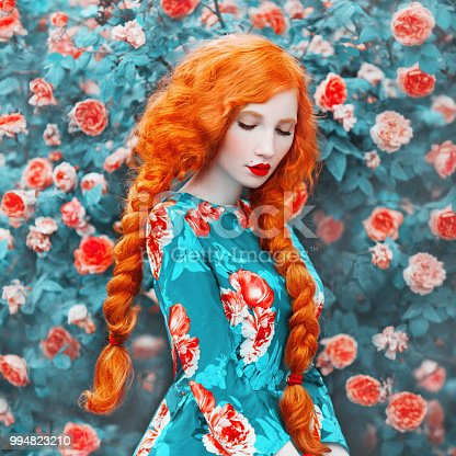 istock Young beautiful redhead girl with very long hair braided in plait on rose background. Fabulous renaissance woman in a flower dress against the backdrop of a beautiful rose bush. Doll with plait 994823210