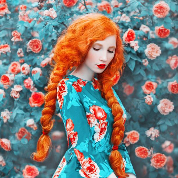 junge schöne rothaarige mädchen mit sehr langen haaren geflochten in zopf auf rosa hintergrund. fabelhafte renaissance-frau in einer blume kleid vor dem hintergrund der schönen rosenstrauch. puppe mit zopf - festliche kleider kindermode stock-fotos und bilder