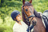 Young beautiful rider woman in helmet holding bay horse by bridle