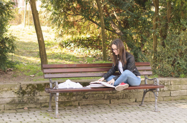 Young beautiful school or college girl with eyeglasses sitting on the bench in the park reading the books and study for exam stock photo
