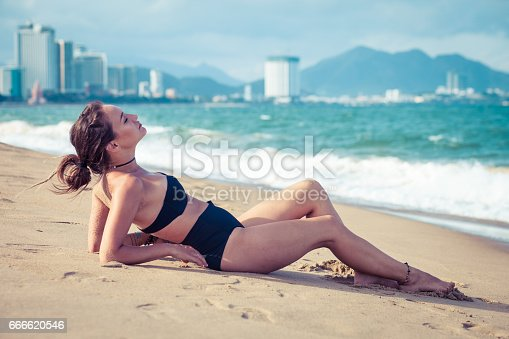 516818180 istock photo Young beautiful sexy brunette bikini model laying on sea beach. Exotic country travel and rest concept. 666620546