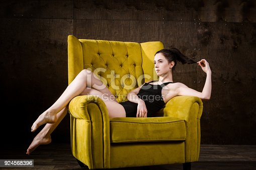 istock A young beautiful, sexy Caucasian woman with thin figure and long bare legs, barefoot posing reclining on yellow armchair in the interior against dark wooden wall. Dressed in a black classic swimsuit 924568396