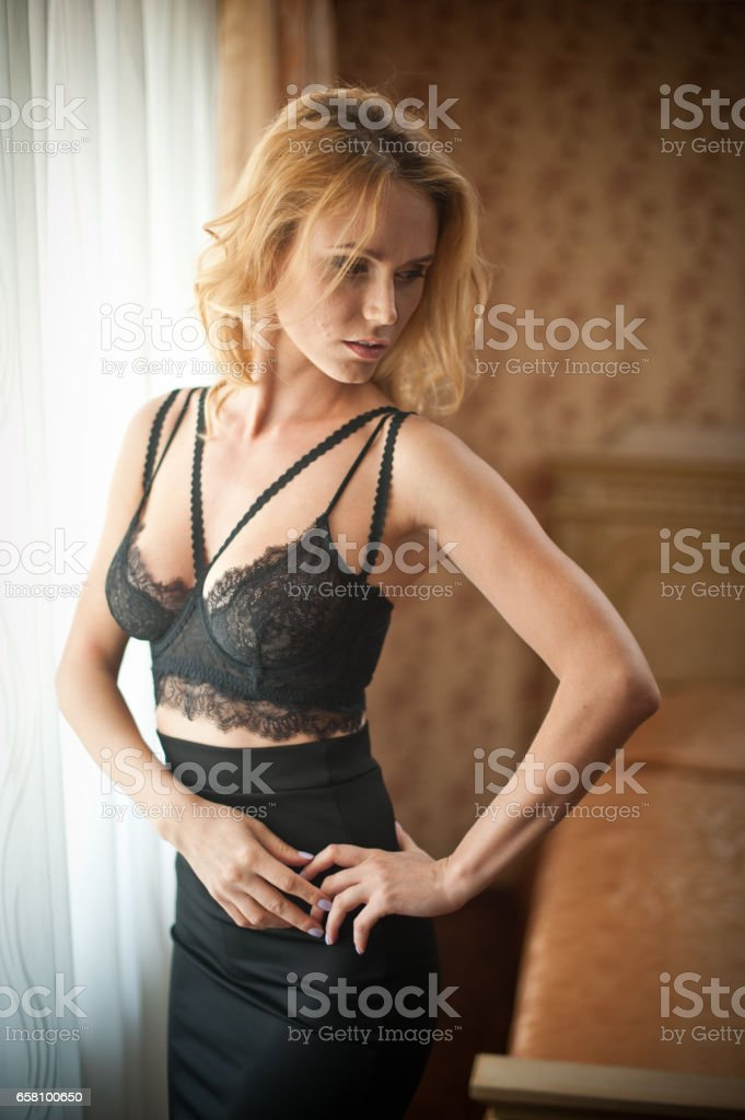 Young beautiful sexy woman in black bra and skirt posing in window light in vintage hotel room. Sensual blonde long hair female staying near a window. royalty-free stock photo