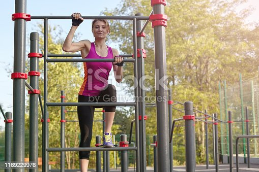 Young beautiful slim woman in bright sportswear climbs up on the ladder at outdoor sportsground. White earphones, protective gloves. Real woman morning training, strength and motivation. Copy space.