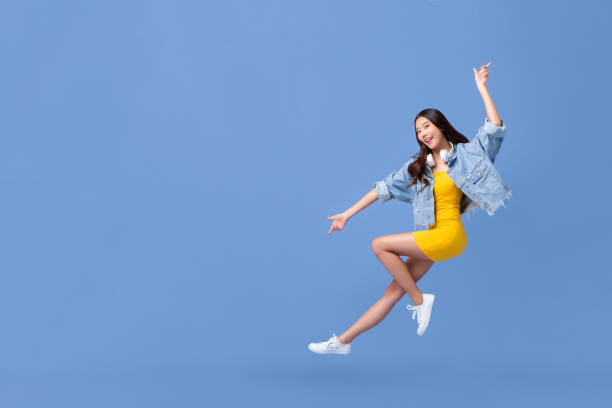 Young beautiful smiling Asian girl floating in mid-air stock photo