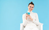 istock Young beautiful smiling female in eyeglasses, dressed in white clothes, sitting in armchair with coffee cup in hands, having rest from work, isolated on blue background 1255734898
