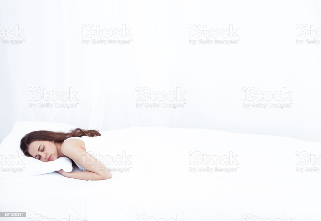 Young beautiful smiling woman is sleeping sweetly in a white bed at...