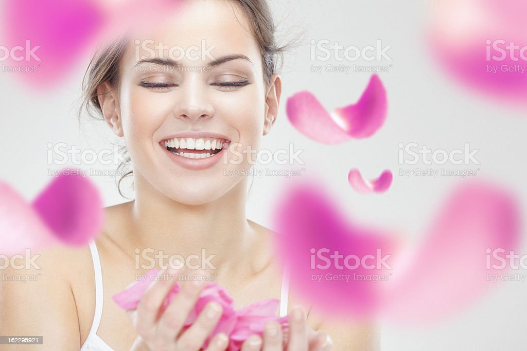 Young beautiful smiling woman surrounded by flying pink rose petals stock photo