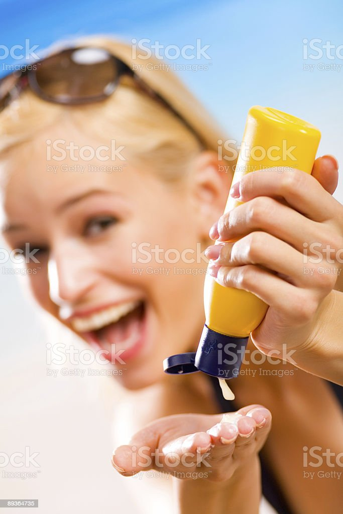 Young beautiful smiling woman with sun-protection cream on the beach royalty-free stock photo