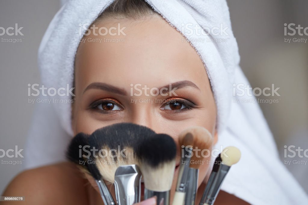 Young beautiful smiling woman with towel on her head holding make-up brushes in her hands. stock photo