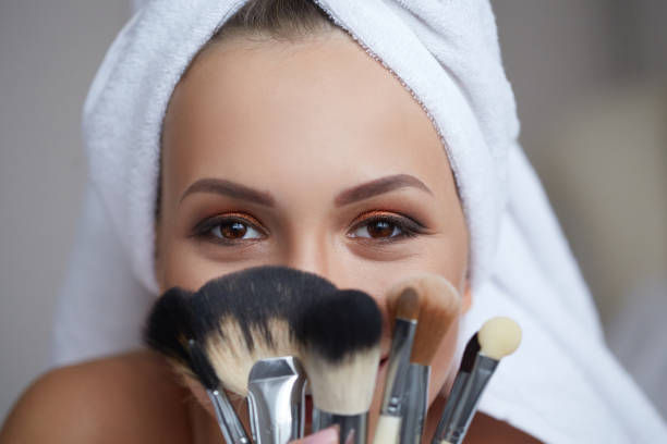 Young beautiful smiling woman with towel on her head holding make-up brushes in her hands. beauty and spa concept make up brush stock pictures, royalty-free photos & images