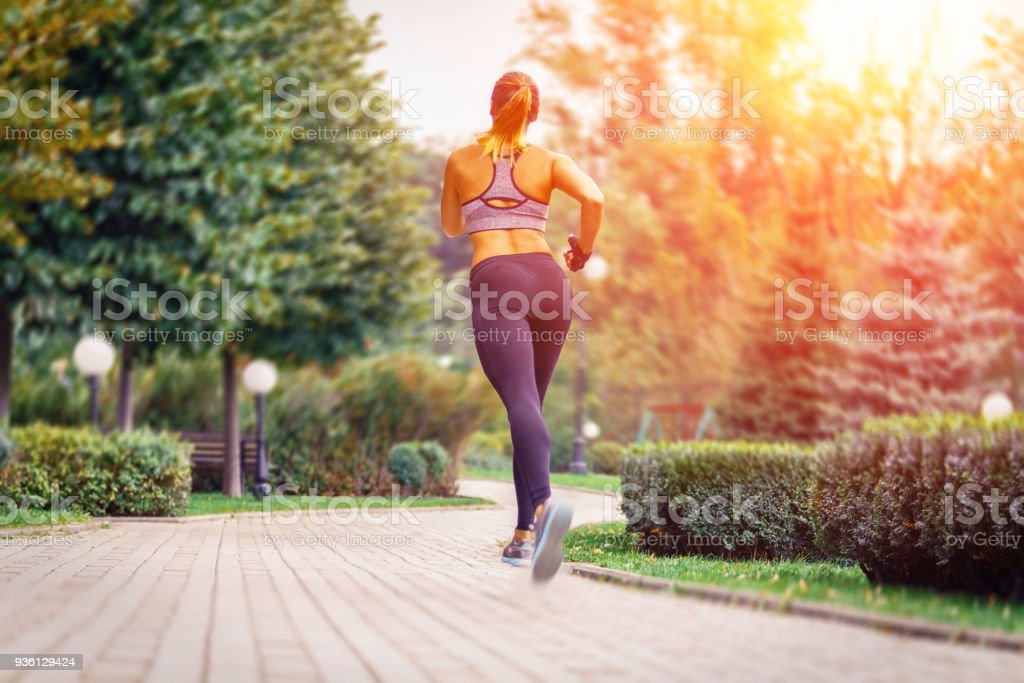 Young beautiful sportive girl runing. view from the back stock photo