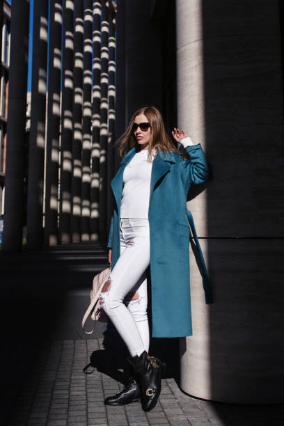 Young beautiful stylish woman walking in blue coat, white jeans and black shoes, holding pink bag in hands, street style, spring summer trend. Fashion season shopping concept stock photo