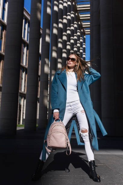 young beautiful stylish woman walking in blue coat, white jeans and black shoes, holding pink bag in hands, street style, spring summer trend. fashion season shopping concept - spring fashion stock pictures, royalty-free photos & images