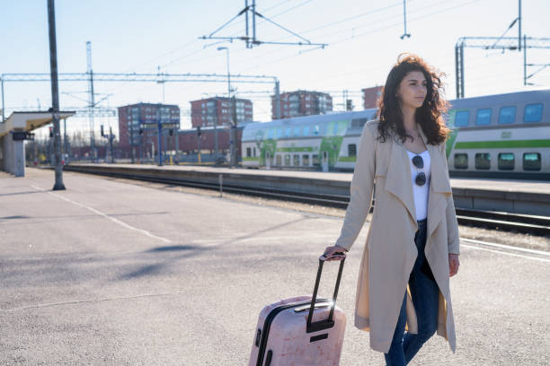 Young beautiful teenage woman with wheeled luggage at train station platform stock photo
