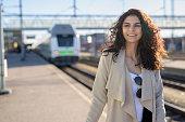 Young beautiful teenage woman with wheeled luggage at train station platform outdoors horizontal shot