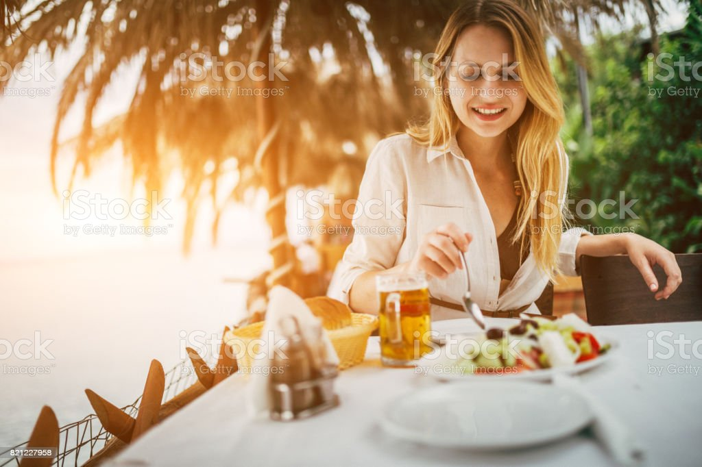 Young beautiful tourist eating mediterranean food in the greek restaurant stock photo