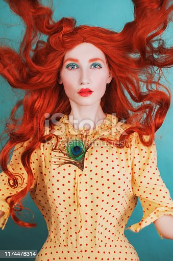 Young beautiful unusual redhead girl with very long curly hair on a blue background. Fairytale model in a yellow dress with an unusual hairdo with a peacock feather. Pale skin. Flying hair
