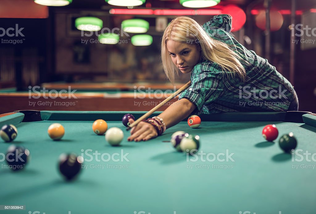 Young beautiful woman aiming at pool ball in a pub. stock photo