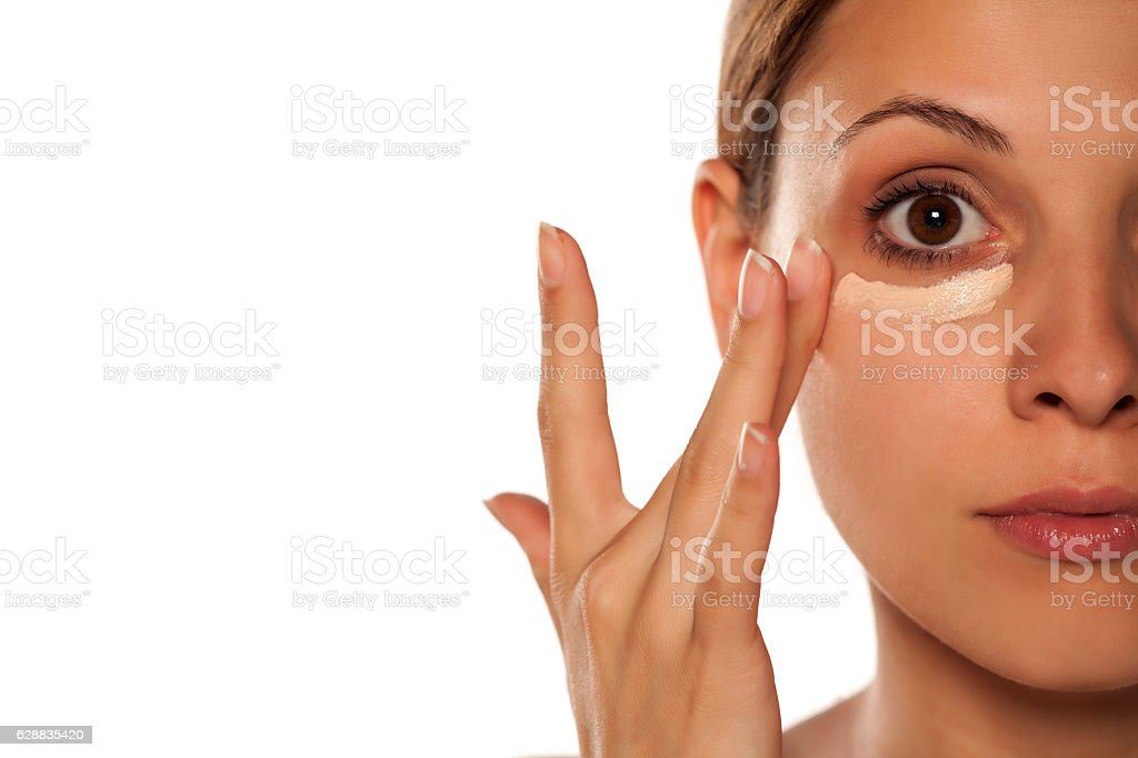 young beautiful woman applied concealer under the eyes stock photo