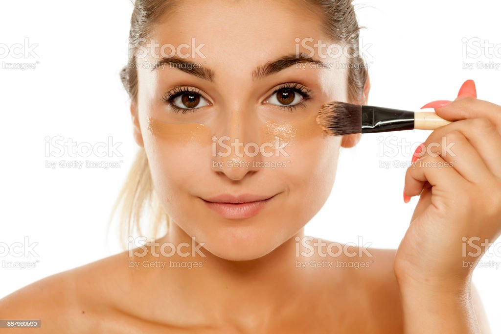young beautiful woman applied liquid base with a brush stock photo