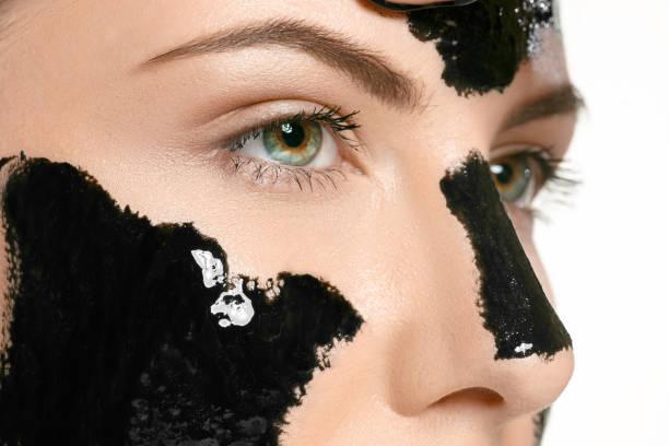 junge schöne frau, eine maske für das gesicht der schwarzen heilschlamm. spa-behandlung - gesicht make up anleitungen stock-fotos und bilder
