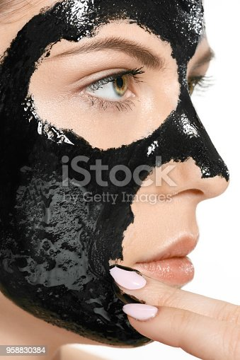 Young beautiful caucasian woman applying a black cosmetic mask for the face of the therapeutic black mud. Spa treatment and face beauty concept. Female face care and perfect skin concepts