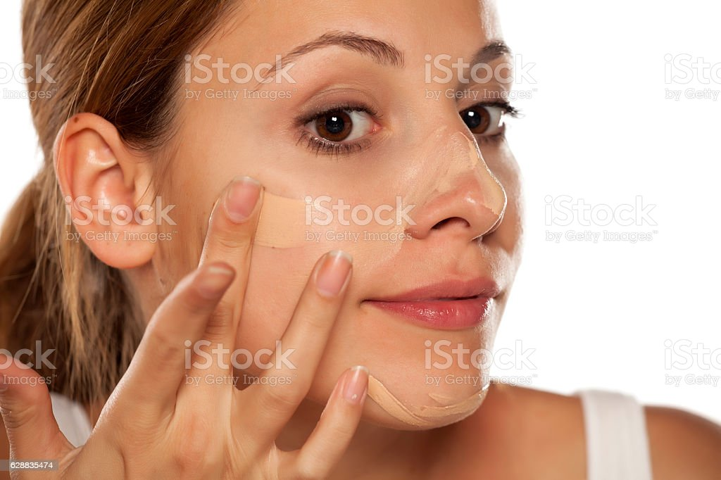 young beautiful woman applying foundation on her face stock photo