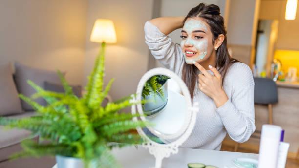 jonge mooie vrouw het toepassen van zelfgemaakte gezichtsmasker thuis - creme huid stockfoto's en -beelden