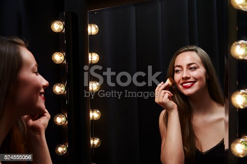 109721176istockphoto Young beautiful woman applying make up in mirror 524555056